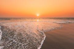 Sunset Sun Above Sea. Natural Sunrise Sky Warm Colors Over Ripple Sea. Ocean Water Foam Washing Sandy Beach At Sunset Stock Image