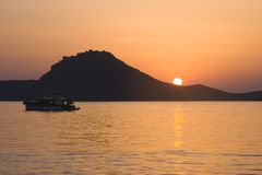 A sunset with sun falling below mountain on the horizon and calm waters in the foreground with boat sailing by stock photos