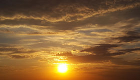 Sunset - sun in gray clouds. Orange sunset - sun in gray clouds Stock Images