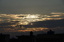 The sunset. The sun hiding behind the clouds stock photos