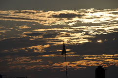 The sunset. The sun hiding behind the clouds royalty free stock photography