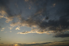 The sunset. The sun hiding behind the clouds stock photography