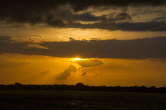 Sunset with sun and raining clouds Royalty Free Stock Photo