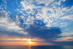 Sunset with sun rays and clouds Stock Photos