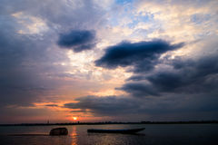 Sunset. The sun sets, the reservoir evening light overcast sky. Fishing boat near the shore Stock Image