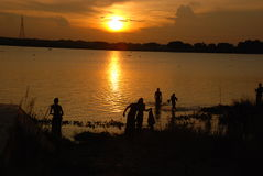Sunset. Sun setting and some people take bath from river Stock Photography