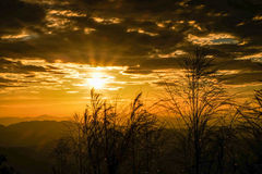 Sunset. Sun shines through the clouds, the mountains Royalty Free Stock Photo