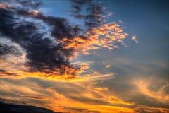 Sunset. The sun shining through cloudy sky Royalty Free Stock Photo