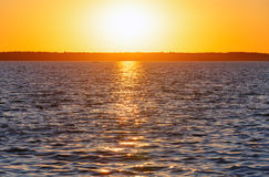 Sunset and sun track on lake surface. Royalty Free Stock Images