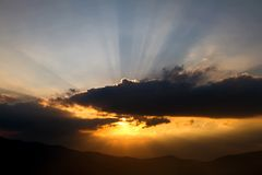 Sunset with the sunbeams over cloud. Sunset into the dark cloud with the sunbeams in the Turkey mountains royalty free stock image