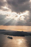 Sunset with sunbeams over Volcano with boat on Santorini island in Greece Royalty Free Stock Images