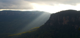 Sunset and sunlight over valley: Blue Mountains. Sunlight streaming through clouds and into a dense forested valley; Blue Mountains, NSW, Australia royalty free stock images