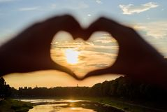 Sunset sunlight romantic atmosphere. Male hands in heart shape gesture symbol of love and romance. Heart gesture in. Front of sunset above river. Summer stock image
