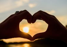 Sunset sunlight romantic atmosphere. Male hands in heart shape gesture symbol of love and romance. Heart gesture in. Front of sunset above river water surface stock image