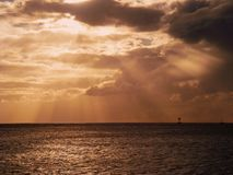 Sunset Sunrays and clouds at the ocean. Sunrays at het ocean give a great orange cloud composition with a ship on the horizon Stock Image