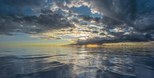 Sunset or sunrise reflected on rippling water. With storm cloud front royalty free stock photos