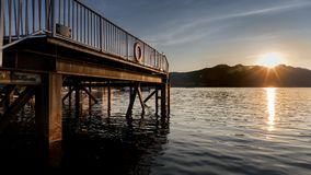 Dock at Lake and Mountain at Sunset or Sunrise Stock Images