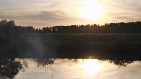 Sunset - sunset in the sky and its reflection in the watery surface of the river. Summer evening. Clubs of smoke in the. Foreground. 4K stock footage