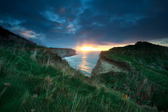 Sunset sunshine over cliffs in ocean Stock Image