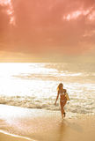 Sunset surfer girl 5. A Beautiful woman walking with surfboard at sunset on a beach with waves breaking in the background 5 Royalty Free Stock Image