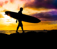 Sunset surfer silhouette. A surfer holding his board walking along the rocks at sunset 2 Royalty Free Stock Image