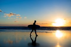 Sunset surfing. Silhouette of man surfer walking with a surf board in his hands across the ocean shore. Sunset surfing. Silhouette of man surfer walking with a Royalty Free Stock Photography