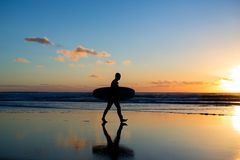 Sunset surfing. Silhouette of man surfer walking with a surf board in his hands across the ocean shore. Sunset surfing. Silhouette of man surfer walking with a Royalty Free Stock Photos