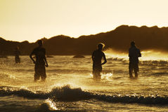 Sunset swimming #1. People playing in the sea at Blouberg beach, South Africa Royalty Free Stock Photo