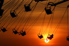 Sunset swings. Swing ride at the kentucky state fair silhouetted against the setting sun royalty free stock photos