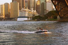 Sports Boat Under the Sydney Harbour Bridge and Cruise Boat in Circular Quay, Australia Royalty Free Stock Image