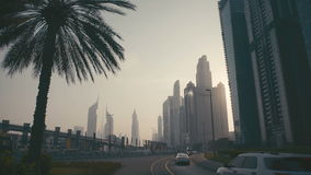 Sunset Tall Building Burj in Dubai. Skyline Cityscape City. Heavy traffic of cars on the road - the highway. Busiest vehicular traffic. Six-lane traffic. Roads stock video