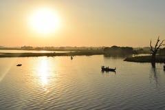 Sunset at Taungthaman Lake, Amarapura, Mandalay, Myanmar. Old gnarled tamarind tree and boats, Taungthaman Lake. Myanmar Stock Photography