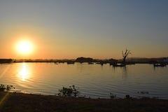 Sunset at Taungthaman Lake, Amarapura, Mandalay, Myanmar. Old gnarled tamarind tree and boats, Taungthaman Lake. Myanmar Royalty Free Stock Photography