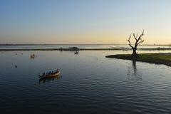 Sunset at Taungthaman Lake, Amarapura, Mandalay, Myanmar. Old gnarled tamarind tree and boats, Taungthaman Lake. Myanmar Royalty Free Stock Photos