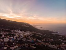Sunset in Tenerife North with the cliff and a rock in the middle of the sea and a town. Picture by drone royalty free stock photography