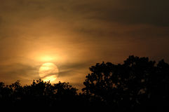 Sunset in Texas. Sun going down over a treeline with a glowing veil of clouds Stock Photography