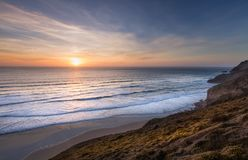 Sunset on th North Cornwall Coast. Sunset over surf on the stunning coast of north Cornwall, with beautiful orange and red hues on the horizon stock image