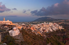 Sunset in Thira of Santorini island. Sunset in Thira town with white and orange buildings on the rock Stock Image