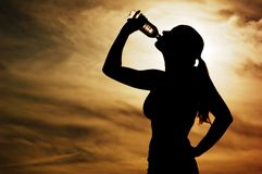 Sunset Thirst. Beautiful young sporty woman drinking in front of a sunset stock photo