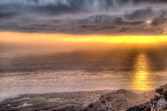 Sunset throwing a glowing pathway across the sea. As it shines from behind a heavy bank of cloud turning the horizon a vivid orange royalty free stock images