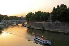 Sunset on the Tiber and Saint Peter, Rome. Sunset on the Tiber, the river of Rome, and it's bridges, with Saint Peter in the backgroud and a boat in foreground Stock Image