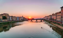 Sunset time in Florence, Italy. Bright sky over Arno river and medieval bridge. Royalty Free Stock Photography