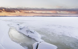 Sunset time next to icy lake Stock Image
