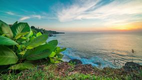 Sunset timelapse on a background of large tropical leaves, rocky coast and ocean on the island of Bali in Indonesia. 4K Timelapse in Bali Island, indonesia stock video