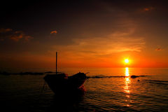 Sunset to the sea with fishing boat. Thailand Stock Photos