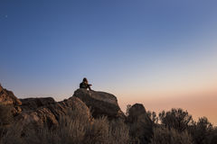 Sunset at the top of Antelope Island in Utah with silhouette of female sitting on rocks Stock Photography