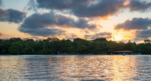 Sunset in Tortuguero - Costa Rica. Yellow sky some clouds. Boat in the foreground stock photo