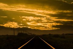 Sunset train tracks. A sunset or sunrise over train tracks royalty free stock photo