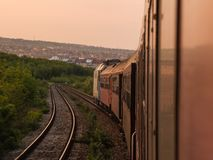Sunset, Train and Travel make a beautiful day. A sunset occurs when the sun descends below the horizon and the light of the day slowly fades. This happens at Royalty Free Stock Images