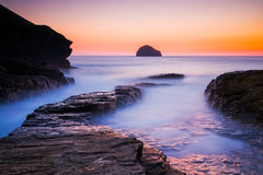 Sunset at Trebarwith Strand Cornwall. Vibrant afterglow illuminates the wet rock at Trebarwith Strand on the North Cornwall Coast royalty free stock photo